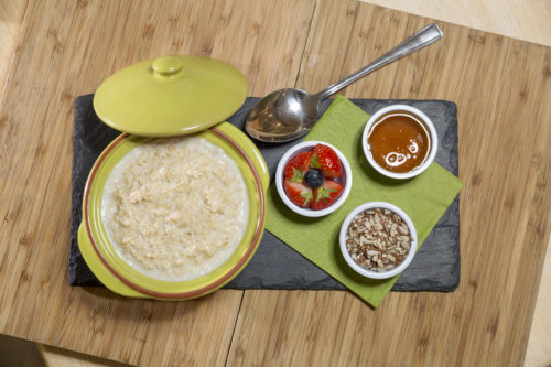 Porridge with honey, strawberries, and grains