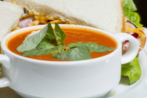 Delicious tomato soup with basil and a sandwich